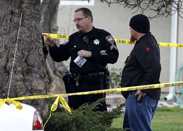 A police investigator holds a photograph of an unidentified man at the scene following a shooting which wounded a federal officer in front of his home in Newark, Calif. on Tuesday, Feb. 7, 2012. Photo: Paul Chinn, The Chronicle