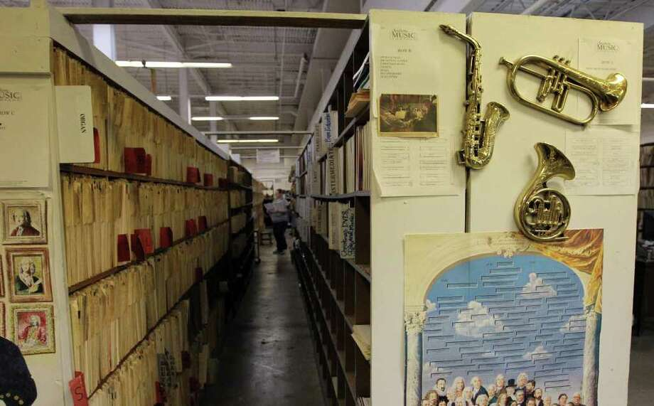 Rebecca Short of Southern Music Co. walks past a row of sheet music on Tuesday, Feb. 7, 2012. The store is going out of business after 75 years. Photo: Kin Man Hui, San Antonio Express-News / San Antonio Express-News