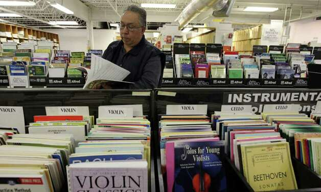 Local musician, Richard Fuentes, looks over sheet music at Southern Music Co. on Tuesday, Feb. 7, 2012. The store is going out of business after 75 years. Through the years it has provided sheet music to all types of musicians. Photo: Kin Man Hui, San Antonio Express-News / San Antonio Express-News