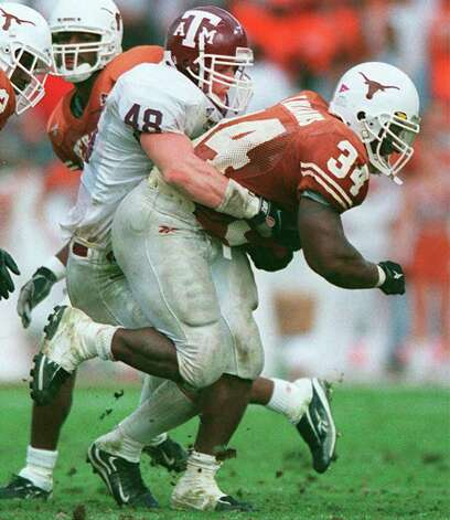 University of Texas' Ricky Williams (34) tangles with Texas A&M's Rich Coady (48) during their game in Austin, Texas on Friday. 11-27-98. Delcia Lopez/staff. Photo: Delcia Lopez, AP/Express-News
