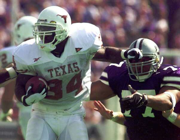 Texas running back Ricky Williams (34) looks for space to run as he tries to avoid the reach of Kansas State tackle Damion McIntosh (77) during the first half Saturday, Sept. 19, 1998, in Manhattan, Kan. (AP Photo/Cliff Schiappa) Photo: CLIFF SCHIAPPA, AP/Express-News / AP