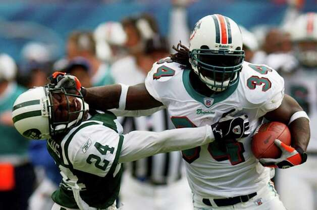 ** FILE **       Miami Dolphins' Ricky Williams (34) tries to avoid New York Jets' Ray Mickens (24) on a 69-yard run  in the first quarter in this Dec. 28, 2003 file photo in Miami. Williams has told the Miami Dolphins that he's retiring after just five years in the NFL, The Miami Herald reported Sunday, July 25, 2004. (AP Photo/Alan Diaz) Photo: ALAN DIAZ, AP/Express-News / AP