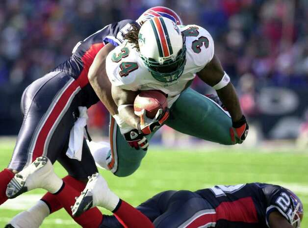 Miami Dolphins' Ricky Williams (34) goes airborne over Buffalo Bills' Nate Clements (22) as he is tackled by Bills' Takeo Spikes (51) during the first half of the game at Ralph Wilson Stadium in Orchard Park, N.Y., Sunday, Dec. 21, 2003. The Dolphins won 20-3. (AP Photo/David Duprey) Photo: DAVID DUPREY, AP/Express-News / AP