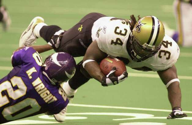New Orleans Saints running back Ricky Williams (34) dives over Minnesota Vikings defensive back Jay Bellamy (20) during first half action in the Louisiana Superdome in New Orleans Sunday Oct. 7, 2001. Williams had a short gain on the play. (AP Photo/Jim Dietz) Photo: JIM DIETZ, AP/Express-News / AP