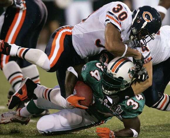 Miami Dolphins runningback Ricky Williams (34), bottom, gets tackled by Chicago Bears linebacker Brian Urlacher, right, and strong safety Mike Brown (30), top, Monday, Aug. 8, 2005 during the second quarter of the Hall of Fame Game in Canton, Ohio.  (AP Photo/Mark Duncan) Photo: MARK DUNCAN, AP/Express-News / AP