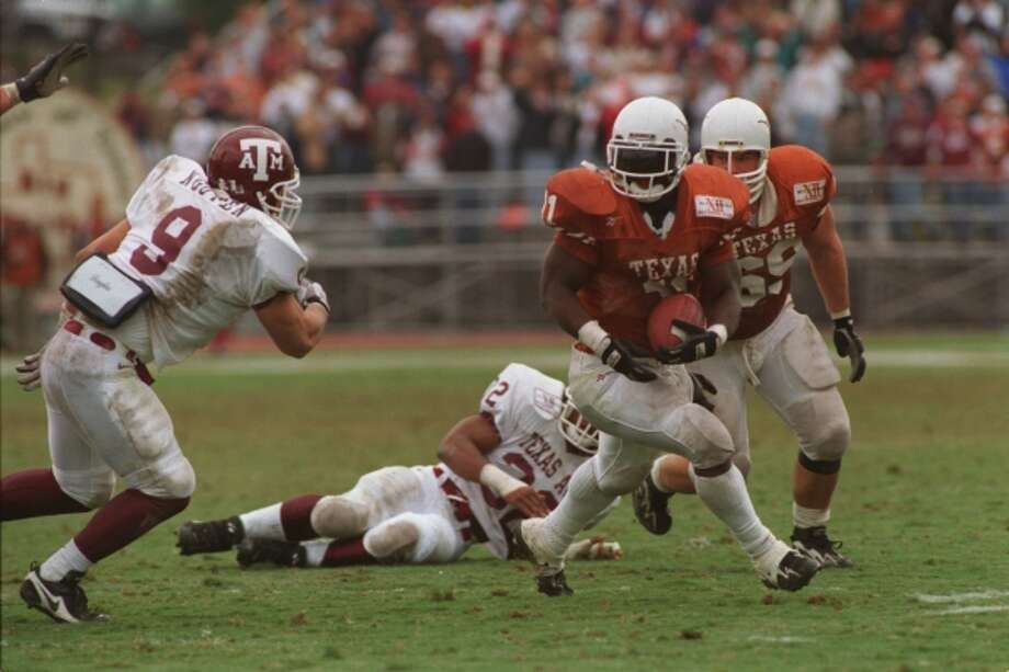 Texas A&M linebacker Dat Nguyen pursues Texas' Ricky Williams in 1996. The Longhorns won the game, 51-15. Williams finished that year with 1,272 yards and 12 rushing touchdowns. (Howard Castleberry / Houston Chronicle)