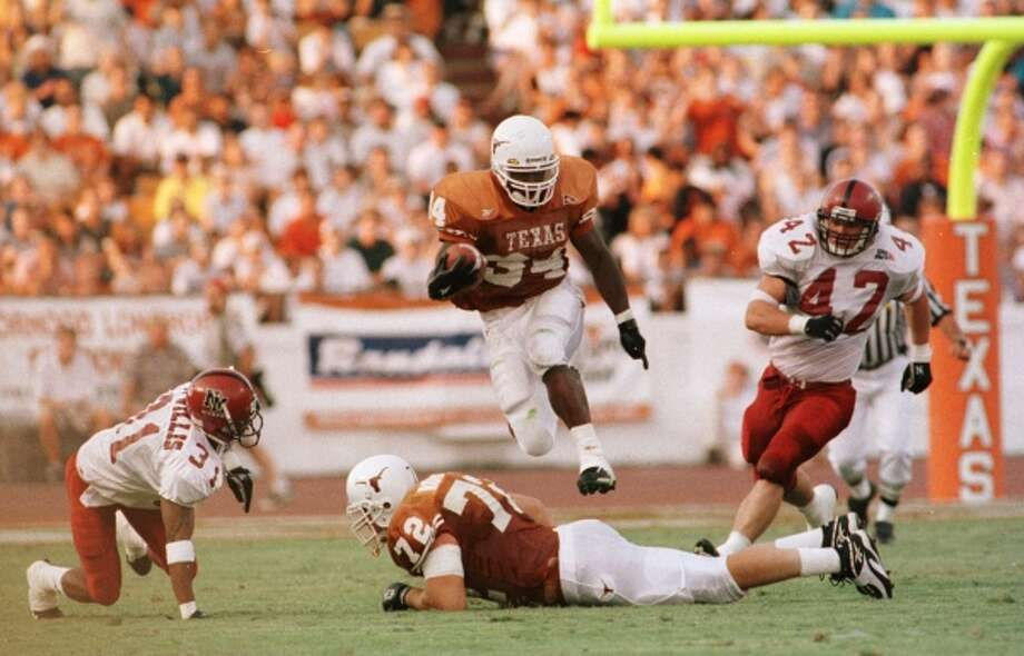 Ricky Williams hurdles teammate Roger Roesler on his way to one of six touchdown runs against New Mexico State on Sept. 6, 1998. (D. Fahleson)