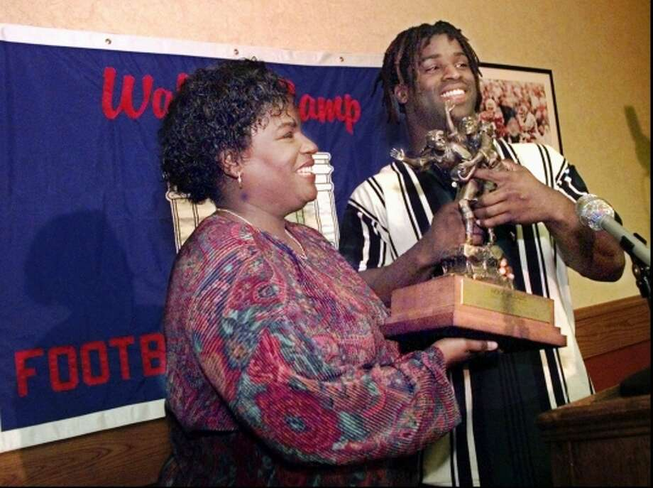 Texas running back Ricky Williams playfully grabs the Walter Camp Award trophy away from his mother, Sandy Williams, during a news conference in the Centennial Room of Bellmont Hall on the Texas campus Monday, Nov. 30, 1998.  (RALPH BARRERA / AP)