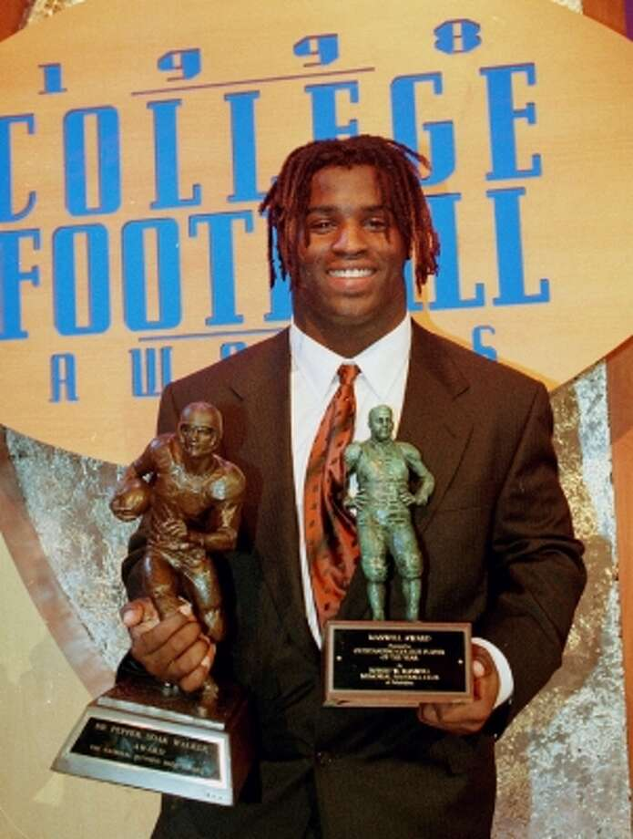 Texas running back Ricky Williams holds the Doak Walker Award and the Maxwell Award, right, after the 1998 College Award ceremonies in Lake Buena Vista, Fla., Thursday, Dec. 10, 1998. (PETER COSGROVE / AP)