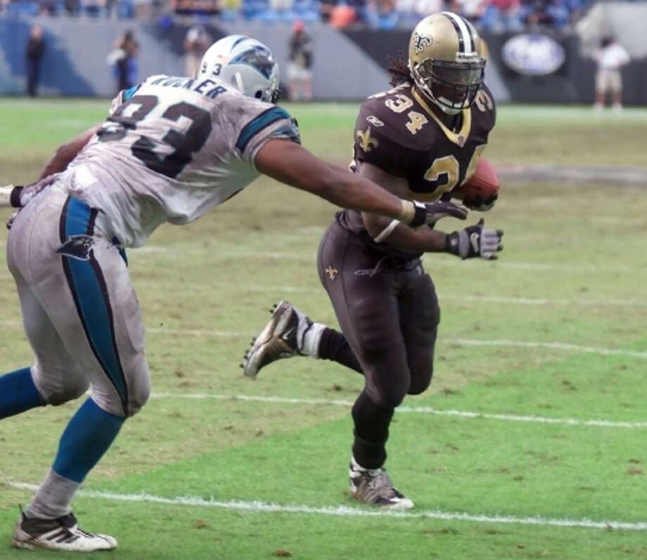 Ricky Williams (34) runs past the Carolina Panthers' Michael Rucker for a one-yard touchdown as time expires to give the Saints a 27-25 win on Oct. 14, 2001, at Ericsson Stadium in Charlotte, N.C. Williams had 1,245 yards rushing that year and scored six times on the ground. (RICK HAVNER / AP)
