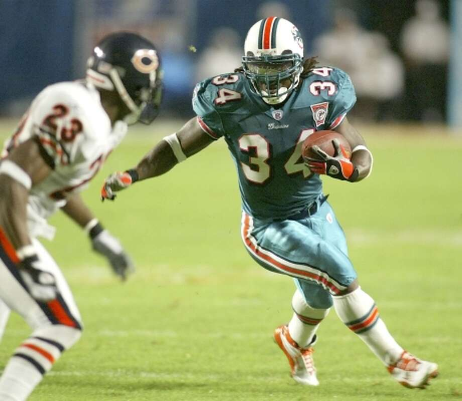 Miami Dolphins running back Ricky Williams runs around Chicago Bears corner back Jerry Azumah during a Dec. 9, 2002, game in Miami. This was Williams' finest season as a pro: he led the NFL in rushing with 1,853 yards and scored 16 touchdowns. He also averaged a league-best 115.8 yards per game.  (GARY I. ROTHSTEIN / AP)