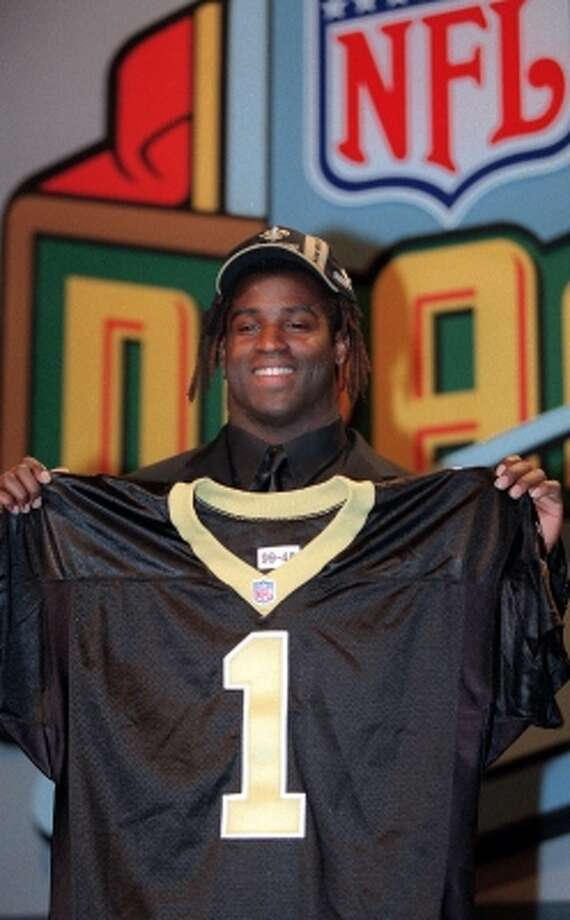 Texas running back Ricky Williams poses with a New Orleans Saints jersey after the Saints made Williams their first pick in the NFL draft and the fifth pick in the draft overall on Saturday, April 17, 1999, in New York. (SUZANNE PLUNKETT / AP)