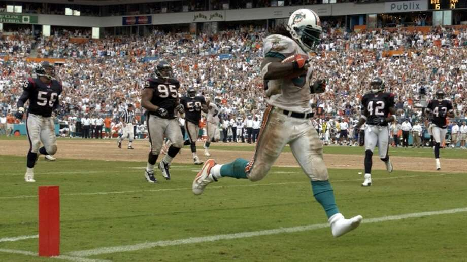 Miami's Ricky Williams scores a touchdown in the fourth quarter despite having one of his shoes torn off on the run. The Texans still won the game, played in September 2003. (Karl Stolleis / Houston Chronicle)