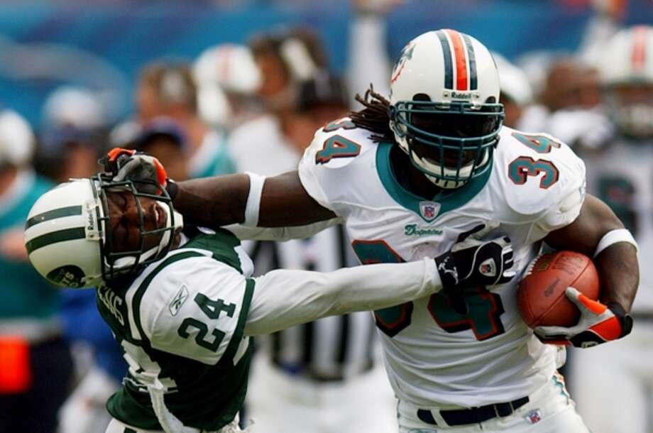 Ricky Williams fends off New York Jets defender Ray Mickens on a 69-yard run on Dec. 28, 2003, in Miami. Williams finished with 1,372 yards and nine touchdowns that season. (ALAN DIAZ / AP)