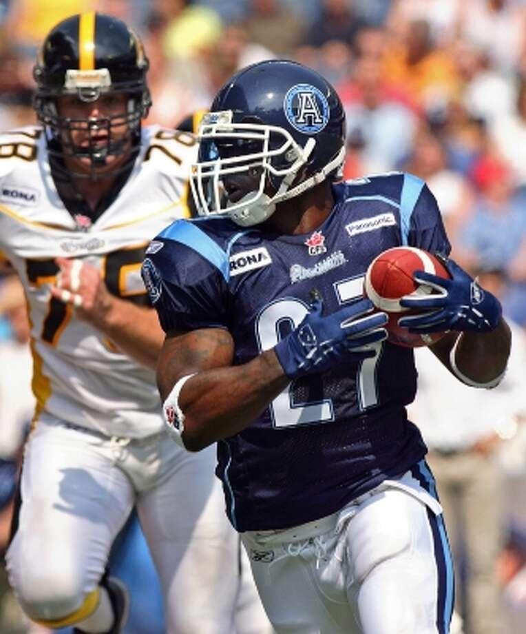 Ricky Williams (27) turns upfield as a running back for the Toronto Argonauts on June 17, 2006, as he is pursued by Hamilton Tiger-Cats defensive tackle Adriano Belli during a CFL game in Toronto. (Frank Gunn / AP)