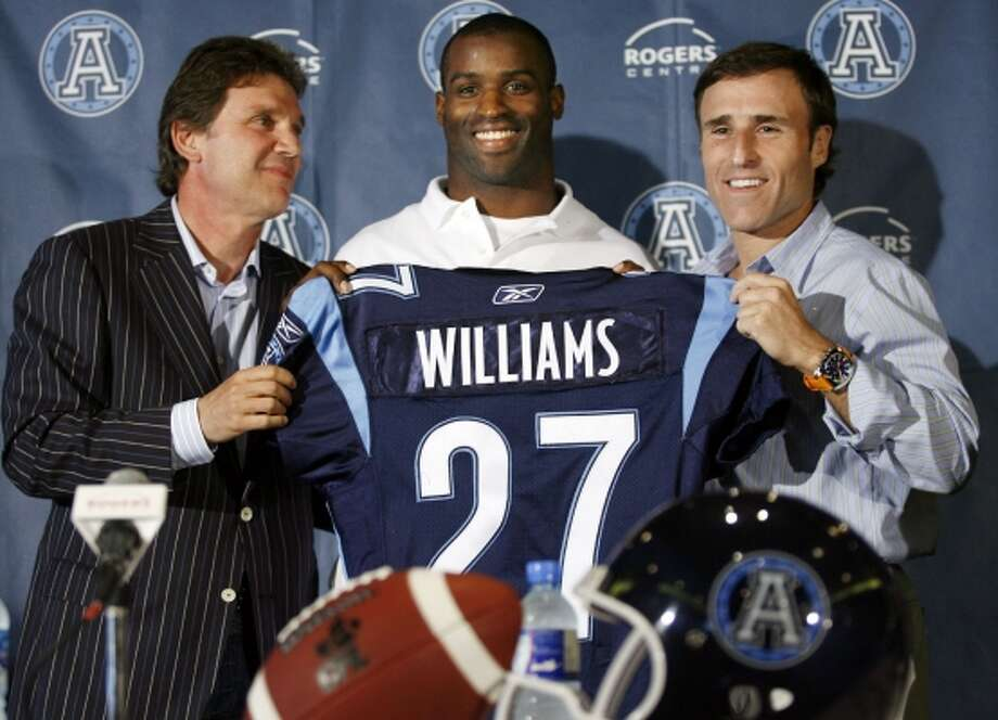 Toronto Argonaut co-owners Howard Sokolowski, left, and David Cynamon flank Ricky Williams during a news conference on May 28, 2006, after the CFL team announced Williams has agreed to play for it in the upcoming 2006 season. Williams, the property of the Miami Dolphins of the NFL, was granted permission by the team to play in Canada following a violation of the NFL's substance abuse program. (HANS DERYK / REUTERS)