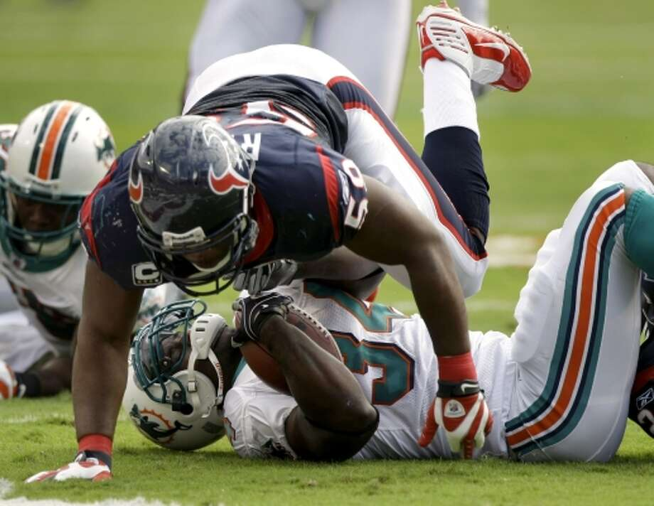 Houston Texans linebacker DeMeco Ryans levels Miami Dolphins running back Ricky Williams at Land Shark Stadium on Dec. 27, 2009. The Texans beat the Dolphins 27-20. This would be Williams' fifth and final season (1,121) with at least 1,000 yards rushing.  (Brett Coomer / Chronicle)