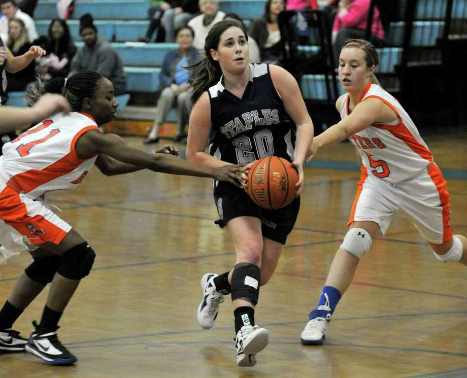 Staples' Remy Nolan drives past Danbury's Uniqua Tucker, left, and Rachel Gartner during their game at Danbury High School on Tuesday, Feb. 7, 2012. Danbury won 45-35. Photo: Jason Rearick / The News-Times