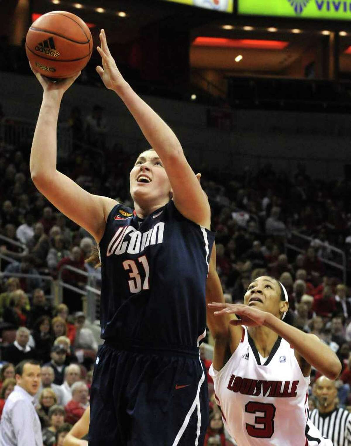 Connecticut's Stefanie Dolson (31) gets a shot off past Louisville's Sherrone Vails (3) during the first half of their NCAA college basketball game Tuesday, Feb. 7, 2012 in Louisville, Ky. (AP Photo/Timothy D. Easley)
