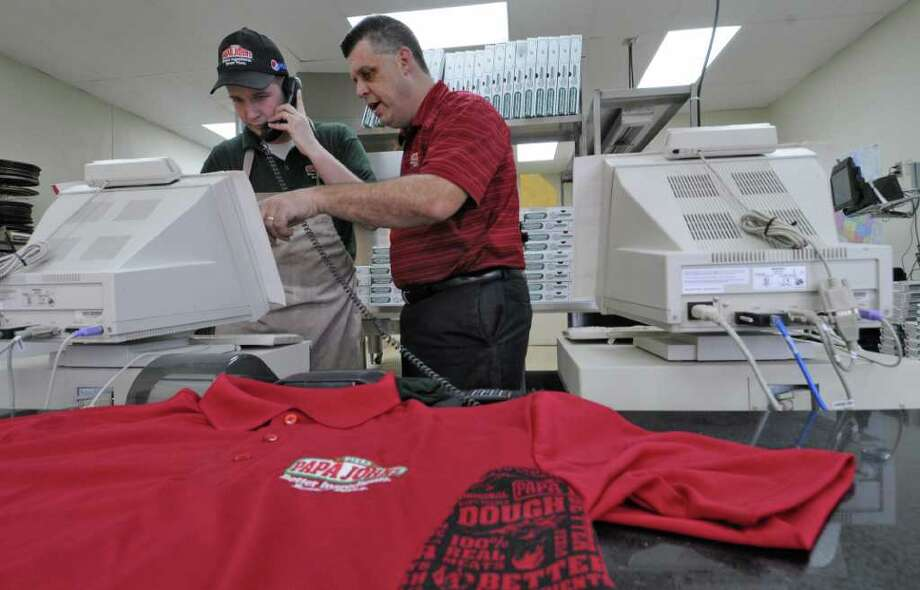 Rick Young, operating partner for the Papa John's pizza on Troy Schenectady Road, right, works with shift leader Jeremy Dudley, near an employee workshirt, on Tuesday Feb. 7, 2012 in Latham, NY.  The state fined the store $5000 for not having enough work shirts for their employees. (Philip Kamrass / Times Union ) Photo: Philip Kamrass / 00016358A