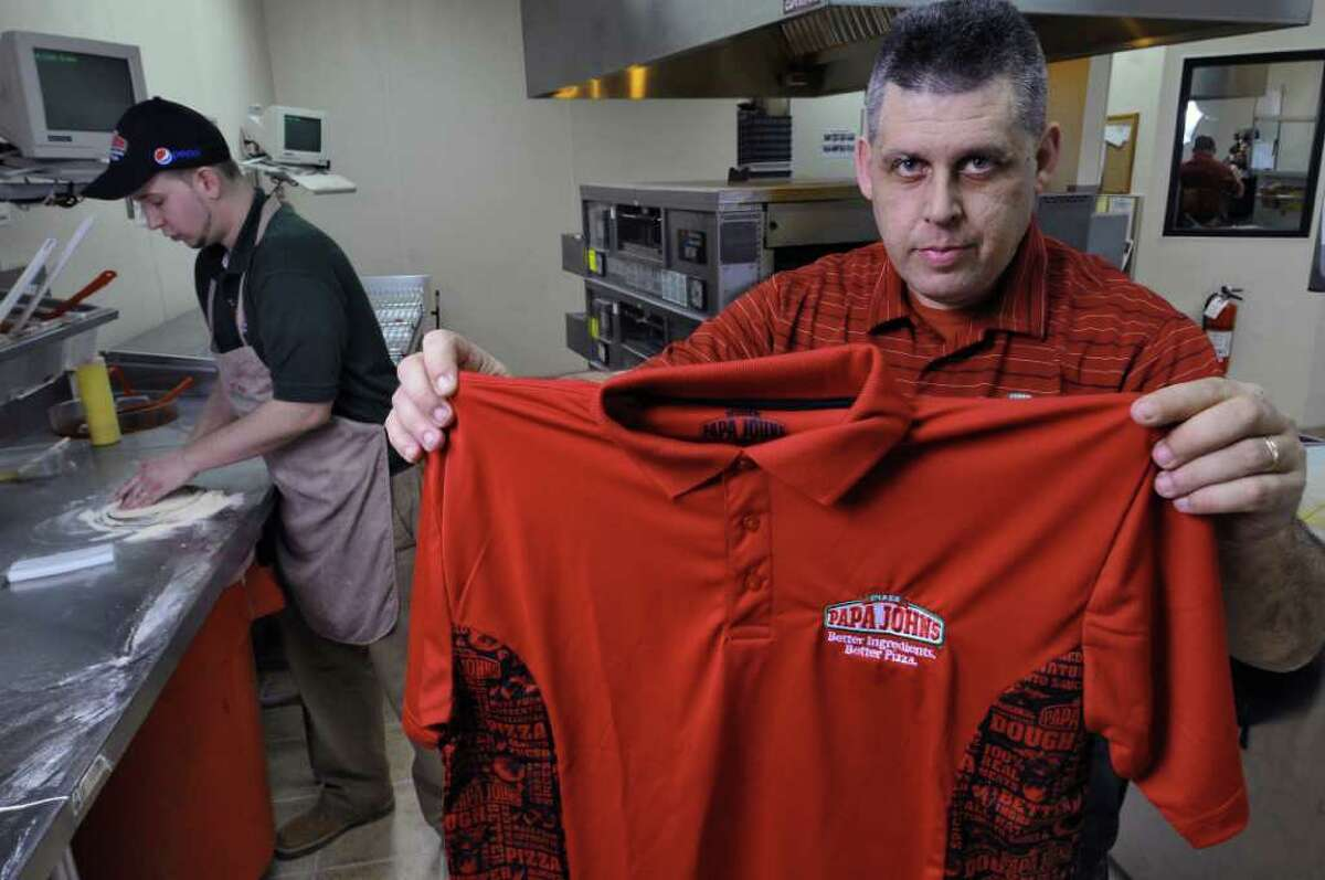 Rick Young, operating partner for the Papa John's pizza on Troy Schenectady Road, holds an employee workshirt, while shift leader Jeremy Dudley, left, makes a pizza, on Tuesday Feb. 7, 2012 in Latham, NY. The state fined the store $5000 for not having enough work shirts for their employees. (Philip Kamrass / Times Union )
