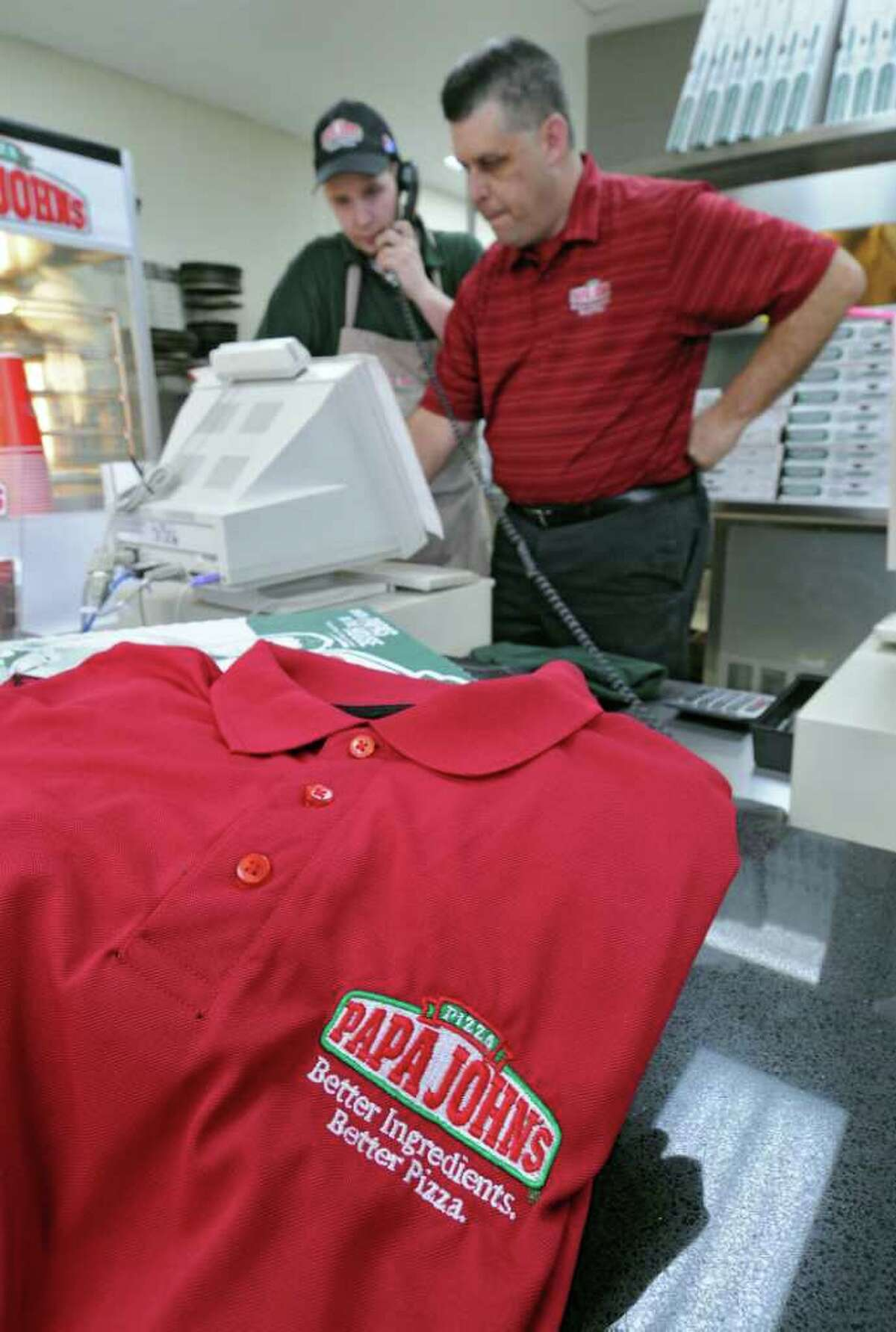 Rick Young, operating partner for the Papa John's pizza on Troy Schenectady Road, right, works with shift leader Jeremy Dudley, near an employee workshirt, on Tuesday Feb. 7, 2012 in Latham, NY. The state fined the store $5000 for not having enough work shirts for their employees. (Philip Kamrass / Times Union )
