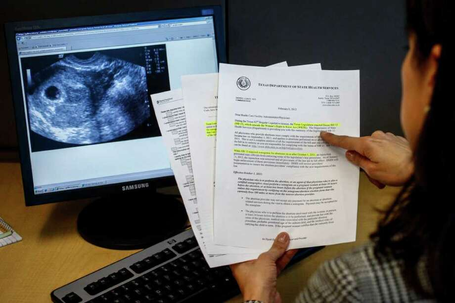 Rochelle Tafolla, an employee at Planned Parenthood, holds paperwork pregnant women are required to sign before undergoing new state-mandated sonograms and having abortions. Photo: Michael Paulsen / © 2012 Houston Chronicle