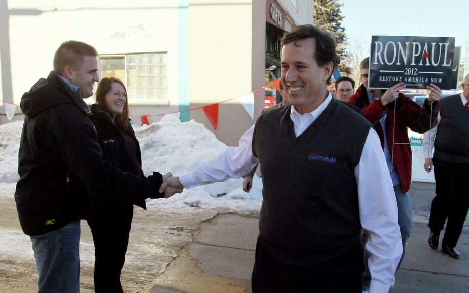 Republican presidential candidate former Pennsylvania Sen. Rick Santorum, shakes hands, as a Ron Paul supporter, right, carries a campaign sign behind Santorum, during a campaign stop at the Bemidji, Minn., Woolen Mills store, the manufacturer of the official Santorum for president sweater vest. Sunday, Feb. 5, 2012. (AP Photo/Charles Rex Arbogast) Photo: Charles Rex Arbogast