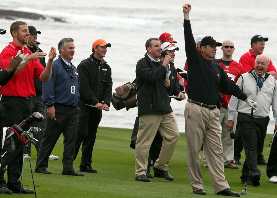 San Francisco 49ers head coach Jim Harbaugh, right, celebrates a favorable kick off a retaining wall that kept his ball in play on the 18th fairway during the charity shootout between the 49ers and the San Francisco Giants at the AT&T Pebble Beach National Pro-Am golf tournament in Pebble Beach, Calif., Tuesday, February 7, 2012. Photo: Lance Iversen, The Chronicle