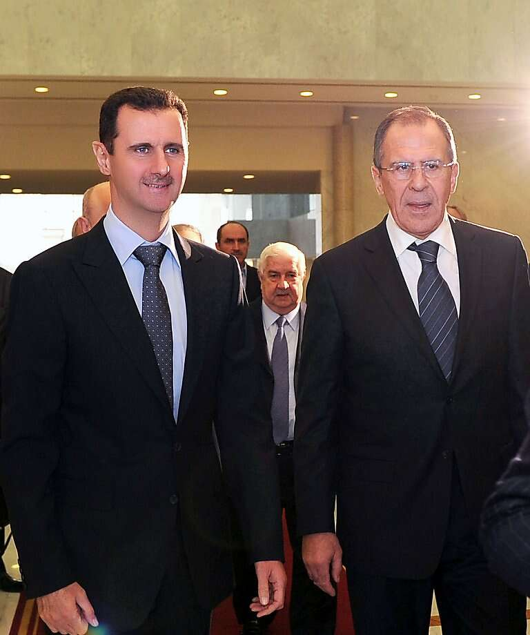 A handout picture released by the Syrian Arab News Agency (SANA) shows Syria's President Bashar al-Assad (L) walking along side Russian  Foreign Minister Sergei Lavrov upong his arival at the presidential palace in Damascus for talks on February 7, 2012.  Lavrov's trip comes days after Russia disgusted the West and Syrian opposition activists by vetoing along with China a UN Security Council resolution condemning the Assad regime's crackdown on protesters. Photo: -, AFP/Getty Images