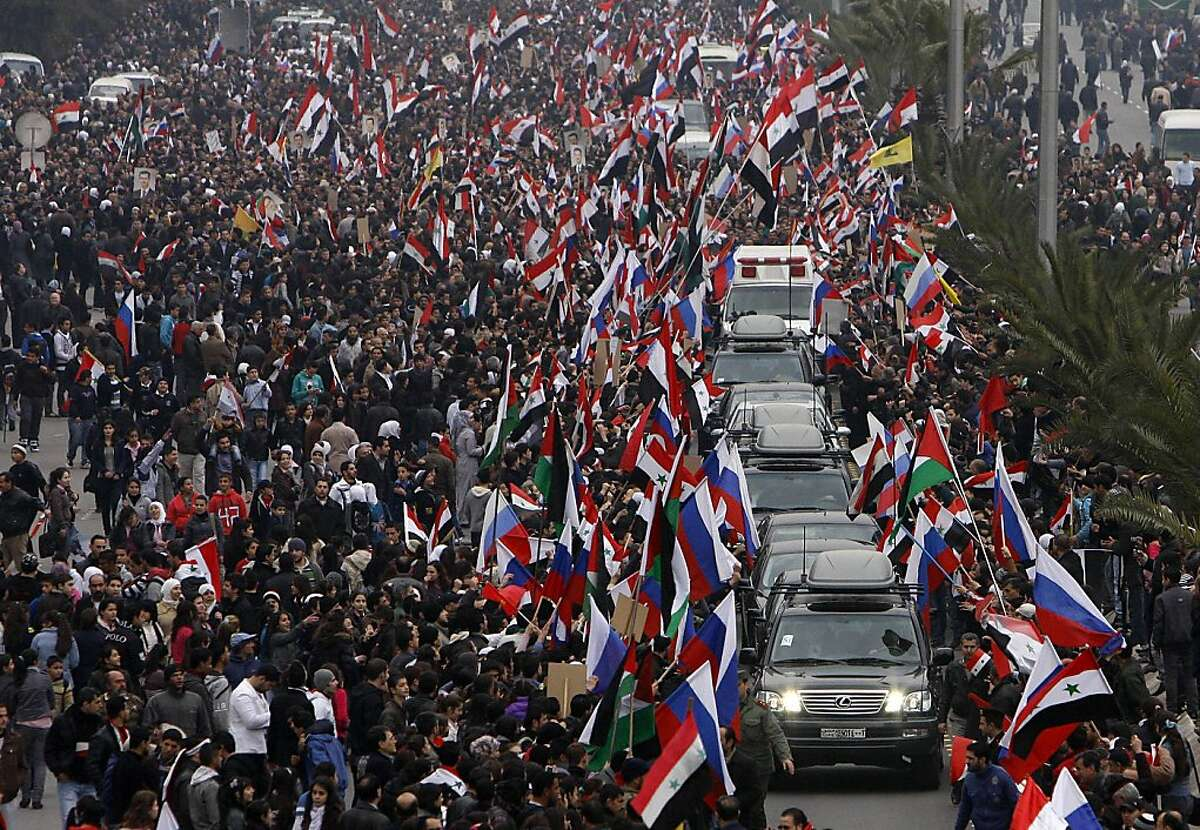 Pro-Syrian regime supporters wave Syrian and Russian flags as they cheer a convoy believed to be transporting Russian Foreign Minister Sergey Lavrov in Damascus, Syria, Tuesday, Feb. 7, 2012. Thousands of Syrians waving Russian flags cheered Russia's foreign minister as he arrived in Damascus Tuesday for talks with embattled President Bashar Assad on the country's escalating violence.