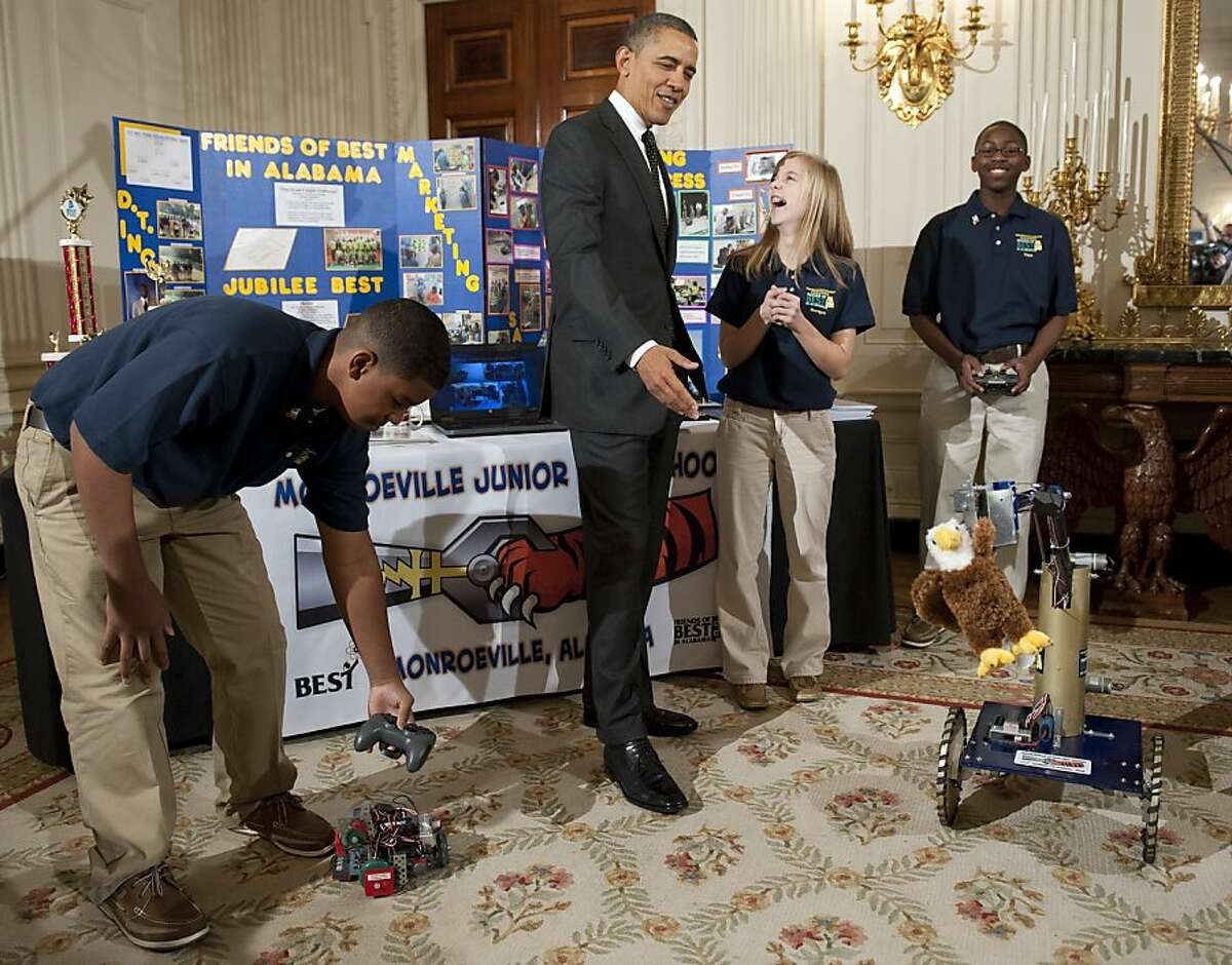 US President Barack Obama speaks with Morgan Ard, Titus Walker and Robert Knight, 8th grade students at Monroeville Junior High School in Monroeville, Alabama, as they demonstrate their award-winning robots during a tour of the White House Science Fair in the State Dining Room of the White House in Washington, DC, February 7, 2012. Obama announced new policies to recruit and support science, technology, engineering and math (STEM) teacher programs, including requesting $80 million in his upcoming budget for teacher preparation, with the goal of training one million additional STEM students over the next decade.