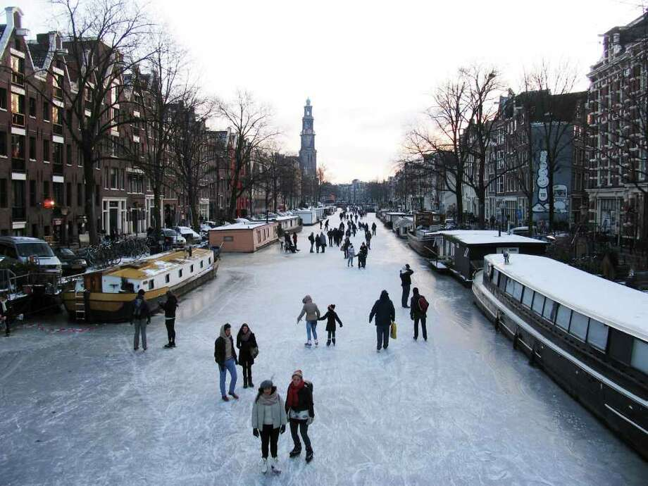 People skate on the frozen Prinsengracht canal in Amsterdam, Netherlands, Wednesday Feb. 8, 2012. In Amsterdam, several of the city's famous canals have frozen over, giving residents a rare opportunity to skate lined by waterfront houses. (AP Photo/Margriet Faber) Photo: MARGRIET FABER, Associated Press / AP