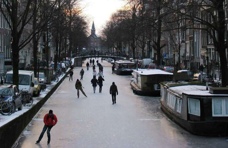 People skate on the frozen Lauriergracht canal in Amsterdam, Netherlands, Wednesday Feb. 8, 2012. In Amsterdam, several of the city's famous canals have frozen over, giving residents a rare opportunity to skate lined by waterfront houses. (AP Photo/Margriet Faber) Photo: MARGRIET FABER, Associated Press / AP