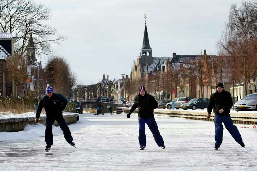 Citizens skate on the frozen De Luts river in Balk, Netherlands, Tuesday Feb. 7, 2012. Volunteers po