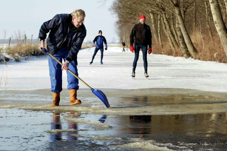 Volunteer Sjoerd Swart shovels away snow from the ice in Oudemirdum, Netherlands, Tuesday Feb. 7, 2012. Volunteers poured onto frozen rivers and lakes in the northern Netherlands on Tuesday to shovel away snow that is one of the major hurdles in the way of a grueling speedskating race called Elfstedentocht, or 11 Cities Tour being held for the first time in 15 years. (AP Photo/Vincent Jannink) Photo: VINCENT JANNINK, Associated Press / AP