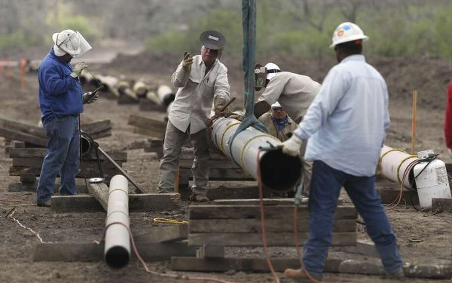 Welding crews lay pipelines east of Karnes City to get oil and gas extracted from the Eagle Ford shale formation to market.