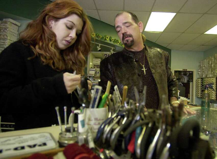 Michael Yuchnitz watches as frame stylist Lavelle Davila replaces a customer's frame Thursday, January 3, 2002.