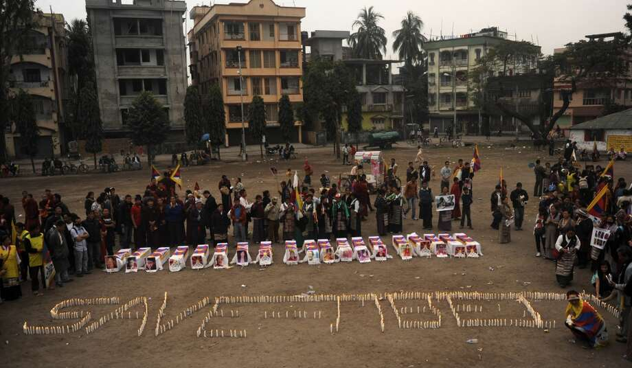 Tibetans offer prayers near mock coffins to represent self-immolated  monks with light candles forming 'Save Tibet' during a rally in Siliguri, India,  on Wednesday. China said February 7 it would 'resolutely crack  down' on any attempts to instigate violence in Tibetan-inhabited areas,  where authorities have launched a deadly clampdown on protesters. (DIPTENDU DUTTA/AFP/Getty  Images)