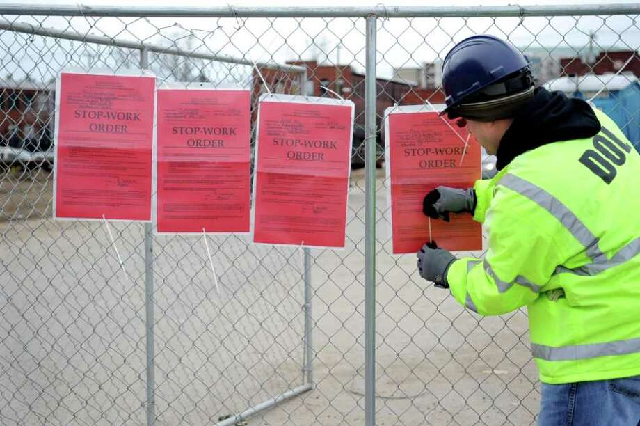 Ariel Morales of the Department of Labor hangs stop work order posters at 555 Pacific Street in Stamford after finding several subcontractors that were not following labor laws working at the site. Photo: Lindsay Niegelberg / Stamford Advocate