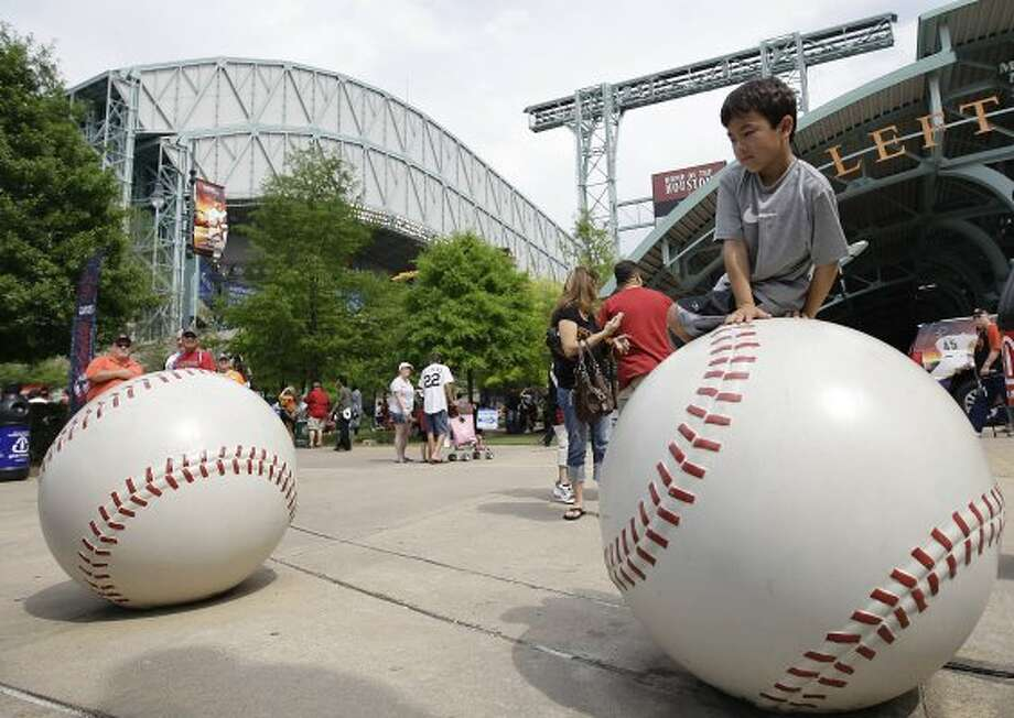 Michael Lee, 7 sits on the giant baseball as fans participate in the Astros' 10th annual opening day street festival before the start of the Astros home opener. (Karen Warren / Houston Chronicle)