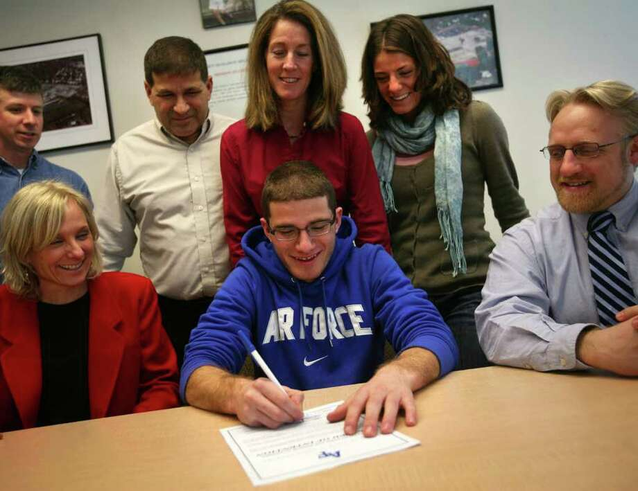 Chris Madaffari signs his National Letter of Intent to attend the Airforce Academy at Brien McMahon High School in Norwalk on Wednesday, January 8, 2012. Surrounding Madaffari from left are coach Jeff Brentson, Principal Suzanne Koroshetz, father Joe, mother Eileen, sister Lauren, and coach Patrick Bradley. Photo: Brian A. Pounds / Connecticut Post