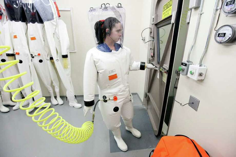 Wearing a protective suit, research assistant Hilary Staples prepares to work in a biosafety level-4 lab. Photo: EDWARD A. ORNELAS, SAN ANTONIO EXPRESS-NEWS / © SAN ANTONIO EXPRESS-NEWS (NFS)