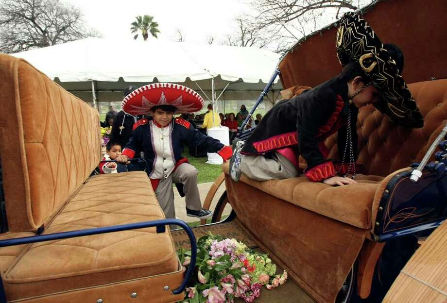 Christopher Hernandez (left), 7, and Juan Torres, 7, climb into a horse-drawn carriage Wednesday as part of a re-enactment of the original Battle of Flowers Parade. Photo: HELEN L. MONTOYA, San Antonio Express-News / ©SAN ANTONIO EXPRESS-NEWS