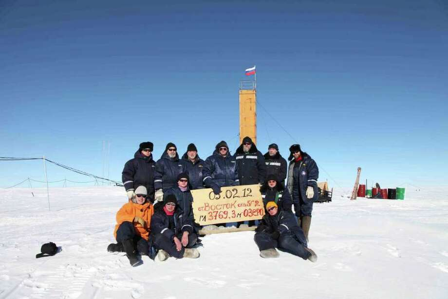 """Researchers at the Vostok station in Antarctica gather for a picture after reaching the subglacial Lake Vostok. The sign being held reads, """"Feb. 5, 2012, Vostok station, bore shaft 5gr, lake at depth 3769.3 meters."""" The Russian team reached the hidden lake Sunday. Photo: Associated Press"""
