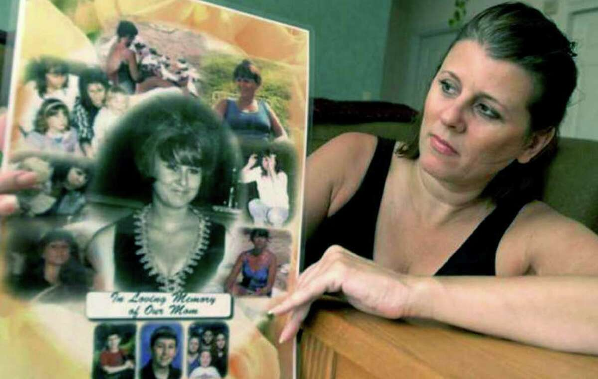 SPECTRUM/Sherrie Passaro of Danbury holds a poster of photographs in memory of her mother, Mary Badaracco, who disappeared from her Sherman home about 27 years ago. 2010