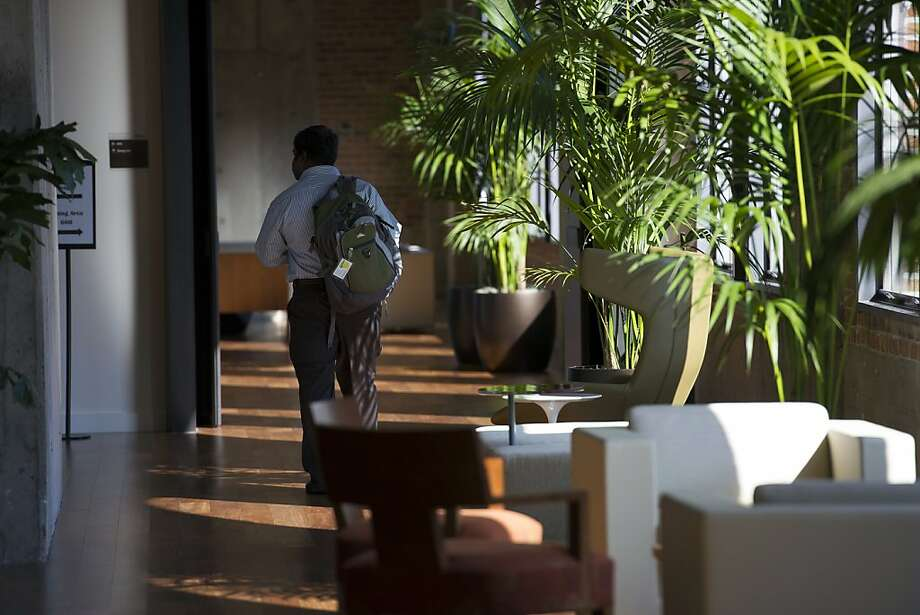 A student walks down the hall at the new location of the University of Pennsylvania's Wharton School. Below: Classrooms in the sixth-floor campus feature large arched windows and tiered seating areas. Photo: David Paul Morris, Bloomberg