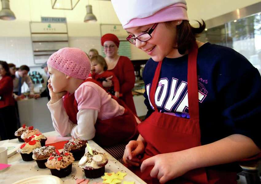 Julia Cobb, 6, left, looks on as Thalia Villalva, 8, right, smiles after decorating her cupcakes at Crave Cupcakes.
