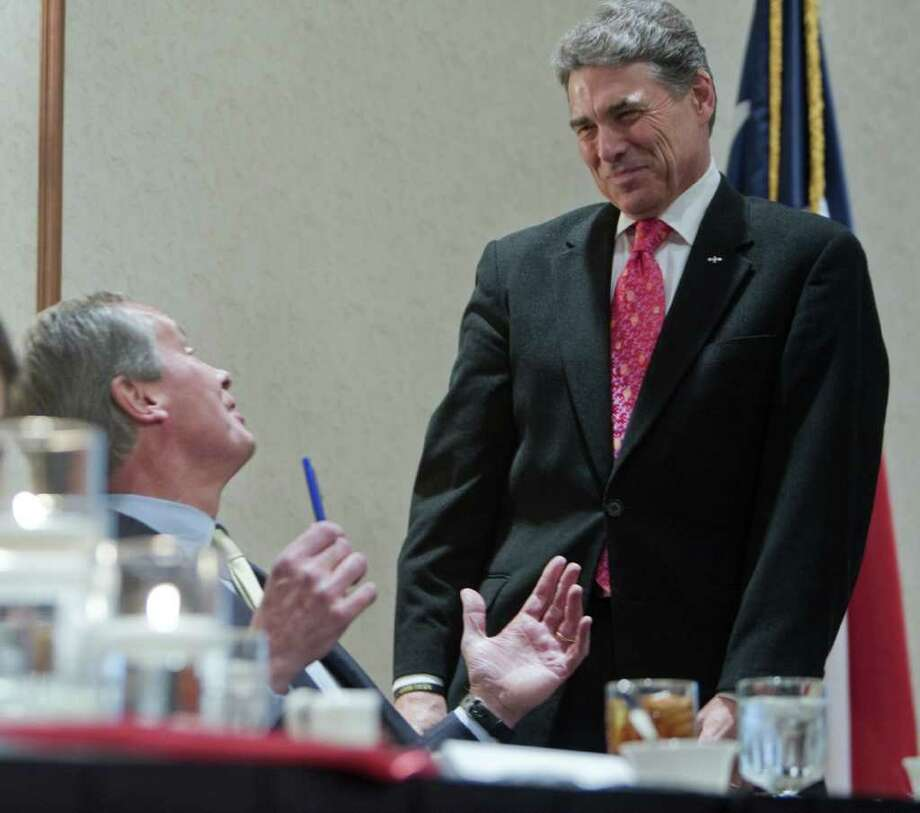 In his first public appearance in Texas since pulling out of the presidential race, Gov. Rick Perry speaks with Lt. Governor David Dewhurst on Monday before the Williamson County Republican party's annual Reagan Dinner in Round Rock. Photo: Ricardo B. Brazziell / Austin American-Statesman
