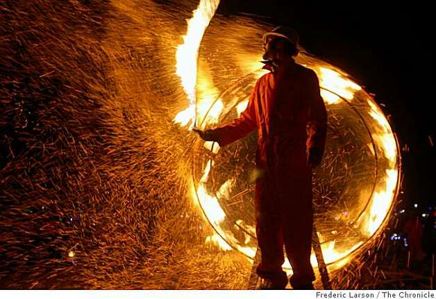 """A performer spins a fire rope in front of the """"Wheel of Thwarted Ambition"""" that also throws off sparks at"""